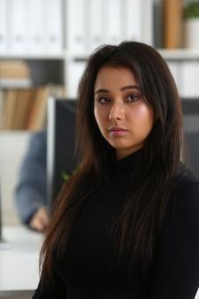 De jonge mooie donkerbruine vrouw zit bij lijst in bureau in kabinet van haar werkgever