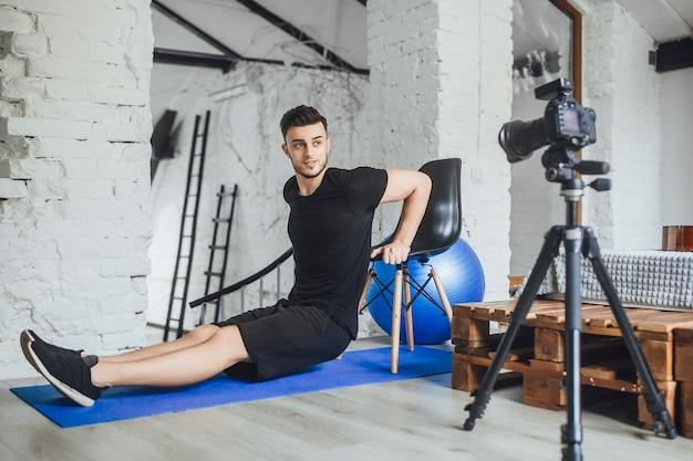De jonge, mooie fitnessblogger schrijft video's voor zijn blog en vertelt over de tools op het werk tijdens een trainingssessie in een kamer in loftstijl