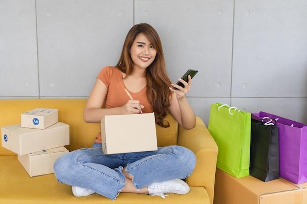 De jonge mooie gelukkige aziatische bedrijfsvrouw in vrijetijdskleding met smileygezicht gebruikt smartphone en schrijvend de naam en het adres van de klant op pakketdoos bij haar starthuiskantoor, mkb-concept