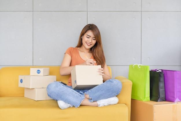 De jonge mooie gelukkige aziatische bedrijfsvrouw met smileygezicht schrijft de naam en het adres van de klant op een pakketdoos verpakking