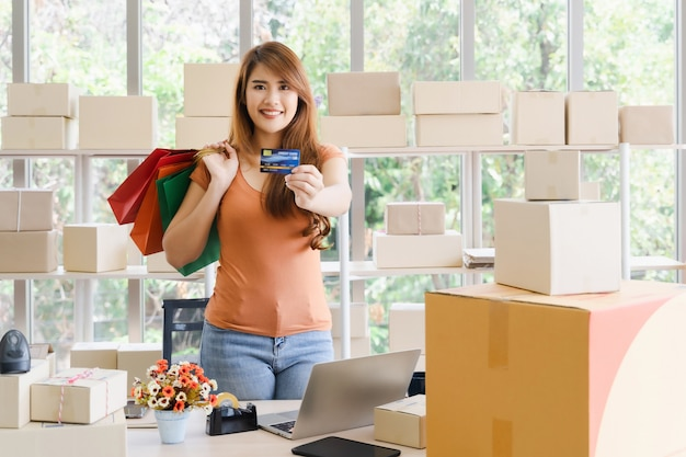 De jonge mooie gelukkige aziatische bedrijfsvrouw met smileygezicht toont creditcard of debetkaart