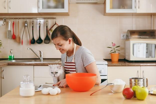De jonge mooie gelukkige vrouw met een witte perzische kat op zoek naar een recept van taarten in een tablet in de keuken. thuis koken. eten koken.