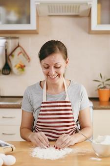 De jonge mooie gelukkige vrouw zit aan een tafel met bloem en gaat een taart in de keuken bereiden. thuis koken. eten koken.