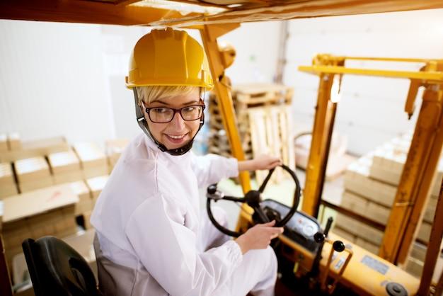 De jonge mooie gelukkige vrouwelijke werknemer drijft vorkheftruck in omgekeerde richting terwijl het dragen van pallet met een stapel kartondozen.