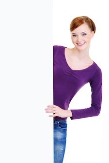De jonge mooie glimlachende vrouw kijkt uit vanwege een lege witte reclamebanner