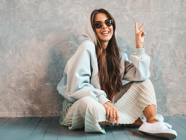 De jonge mooie glimlachende vrouw toont vredesteken. trendy meisje in casual zomer hoodie en rok kleding.