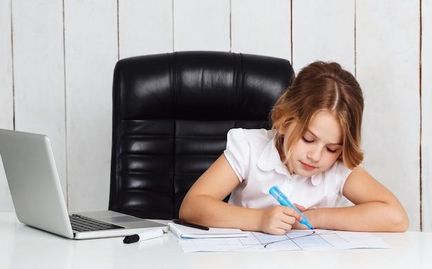 De jonge mooie grafiek van de meisjestekening op werkende plaats in bureau.