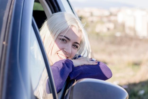 De jonge mooie jonge auto die van de vrouwenzitting uit venster het glimlachen kijken