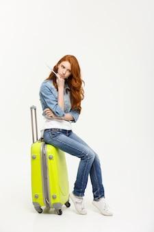 De jonge mooie kaukasische vrouw zit op suitecase en wacht op haar vlucht.