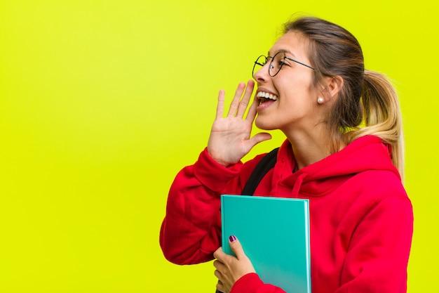 De jonge mooie mening die van het studentenprofiel gelukkig en opgewekt kijkt schreeuwend en roepend om ruimte aan de kant te kopiëren