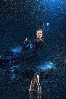 De jonge mooie moderne danser dansen onder waterdruppels