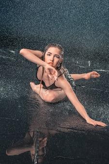 De jonge mooie moderne danser die onder waterdalingen danst