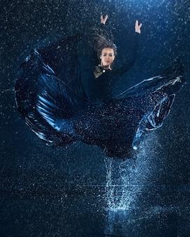 De jonge mooie moderne danseres dansen onder waterdruppels