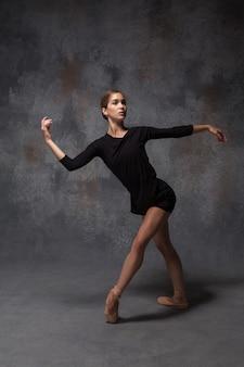 De jonge mooie moderne stijldanser die zich voordeed op een studio grijze achtergrond