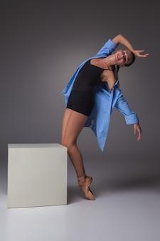 De jonge mooie moderne stijldanser die zich voordeed op witte kubus op een studio grijze achtergrond