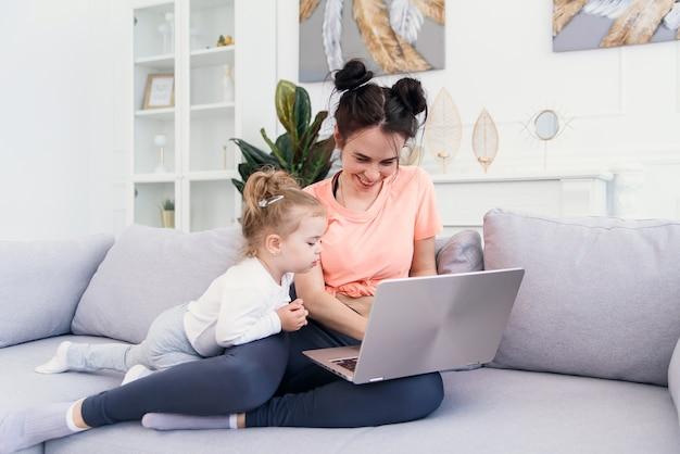 De jonge mooie moeder en haar kleine gelukkige dochter gebruiken laptop en glimlachen terwijl het zitten op bank thuis