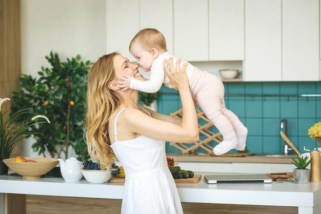De jonge mooie moeder kookt en speelt met haar babydochter in een moderne keuken het plaatsen.