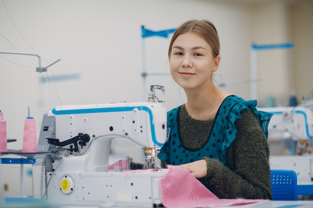 De jonge mooie naaister naait op naaimachine in fabriek