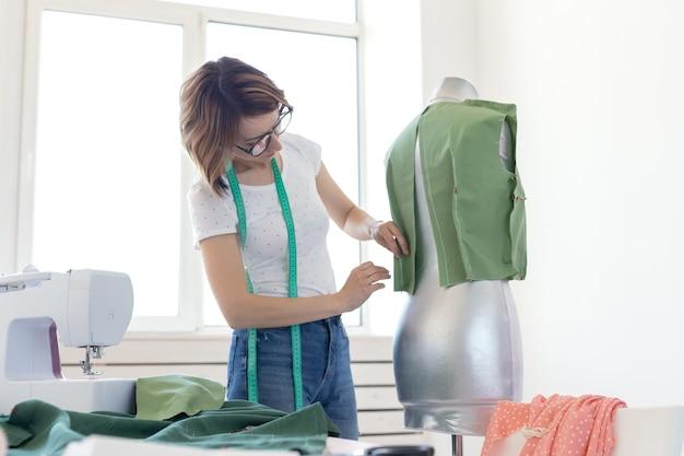 De jonge, mooie naaisterontwerper van het meisje met een bril en een meetlint maakt een nieuw product met behulp van een groene doek en een kleermakerspop. concept van naaiatelier.