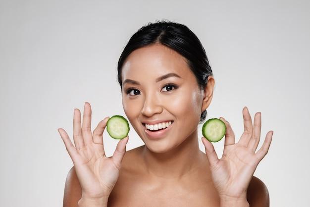 De jonge mooie plakken van de dameholding van komkommer
