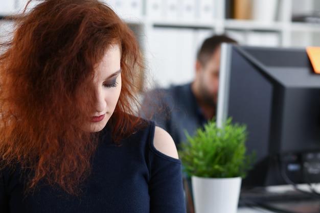De jonge mooie roodharige vrouw zit aan tafel in het kantoor in het kabinet van haar baas