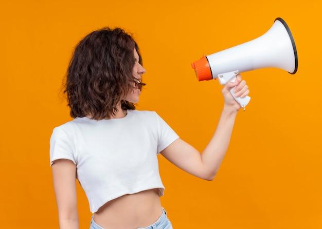 De jonge mooie spreker van de meisjesholding en pratend op geïsoleerde oranje achtergrond