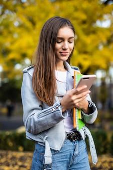 De jonge mooie studente bladerde op mobiele telefoon lopend in stadsstraat Gratis Foto