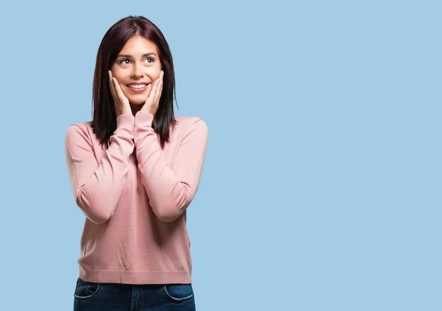 De jonge mooie verrast en geschokte vrouw, kijkend met brede ogen, opgewekt door een aanbieding of door een nieuwe baan, wint concept