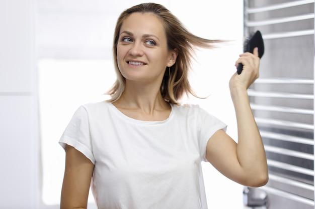 De jonge mooie vrouw bekijkt haar gedachtengang in badkamers en kamt haar haar. vrouw haarstyling thuis concept.