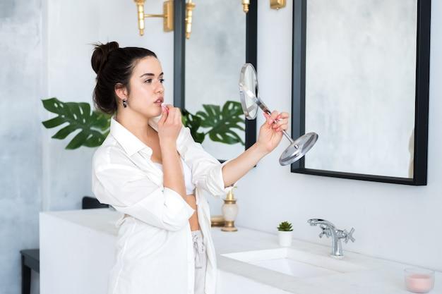 De jonge mooie vrouw bevindt zich in de badkamers, zet op lippenstift en kijkt in de spiegel.