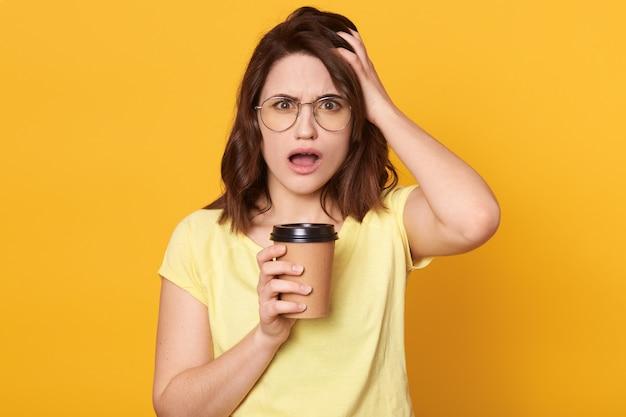 De jonge mooie vrouw die glazen en de toevallige t-shirtholding dragen haalt koffie weg