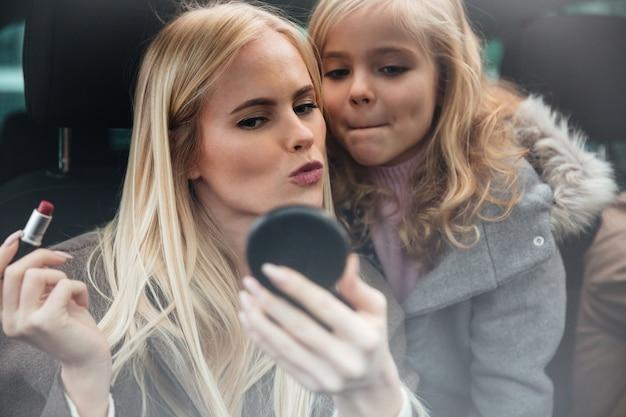 De jonge mooie vrouw die make-up doet bekijkt spiegel