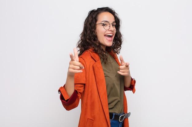 De jonge mooie vrouw die met een positieve, succesvolle, gelukkige houding glimlachen die naar de camera richten, die kanon maken ondertekenen met overhandigt witte muur