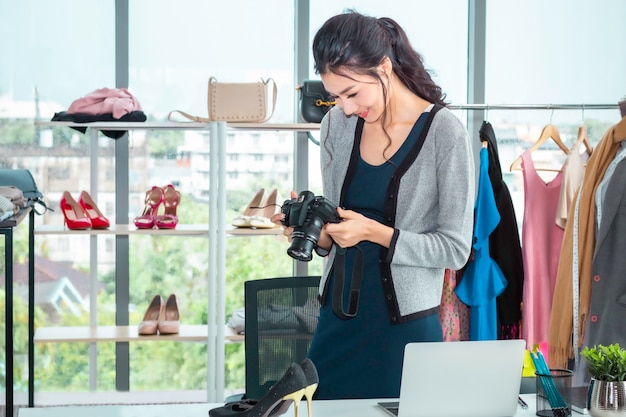 De jonge mooie vrouw die van azië een foto nemen en online elektronische handel werken die bij kleren winkelen winkelen.