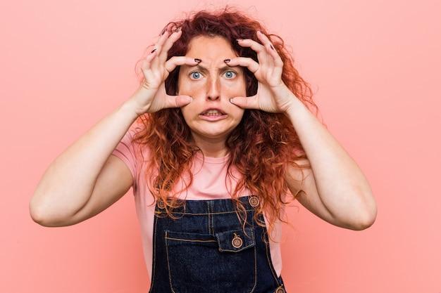 De jonge mooie vrouw die van de gemberredhead een jeansdungaree draagt die ogen houdt geopend om een succeskans te vinden.