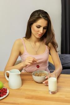 De jonge mooie vrouw eet ontbijtgraangewas met bessen en melk.