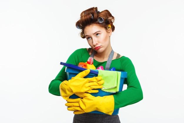 De jonge mooie vrouw houdt schoonmakende hulpmiddelen met droefheid op gezicht