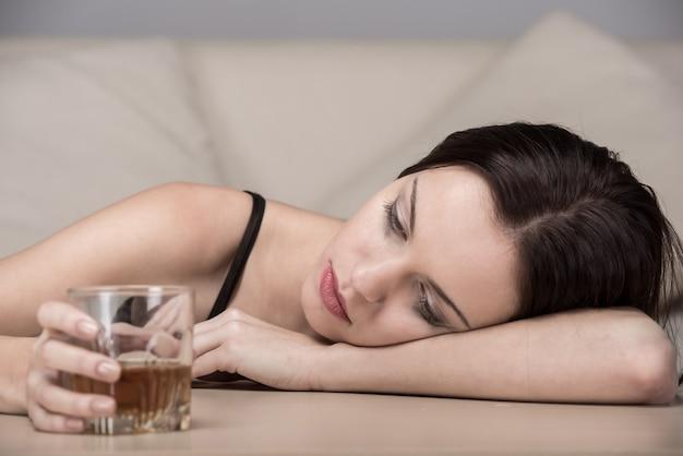 De jonge mooie vrouw in depressie drinkt alcohol.