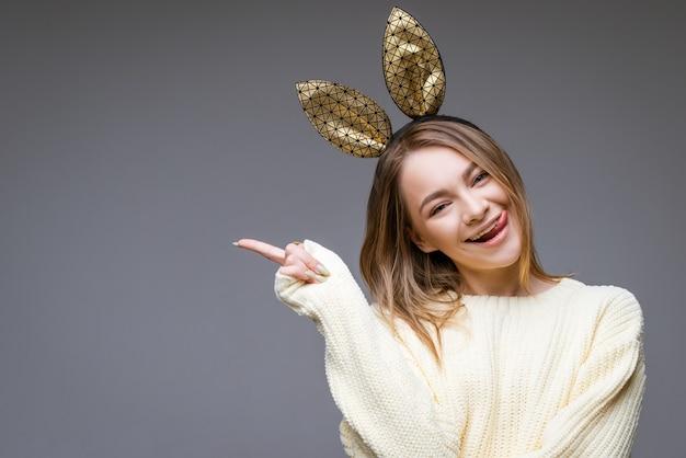 De jonge mooie vrouw in gouden konijnenoren toont tong en vinger aan de kant op grijze muur