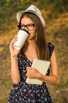 De jonge mooie vrouw in hoed en glazen drinkt koffie.