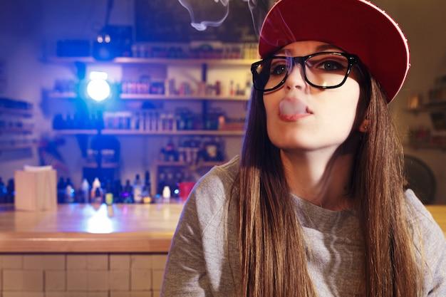 De jonge mooie vrouw in rood glb rookt een elektronische sigaret bij de vape-winkel. detailopname.