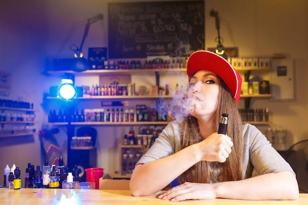 De jonge mooie vrouw in rood glb rookt een elektronische sigaret bij de vape-winkel