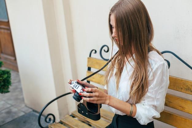 De jonge mooie vrouw kijkt foto's met haar camerazitting op de bank in de zomer