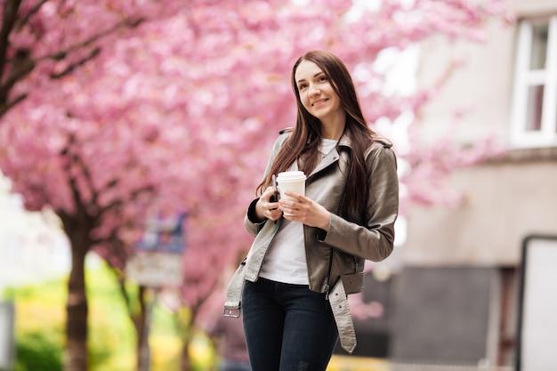 De jonge mooie vrouw met lang donker haar geniet van de schoonheid van de lenteaard dichtbij de bloeiende sakuraboom