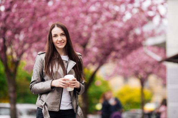 De jonge mooie vrouw met lang donker haar geniet van de schoonheid van de lenteaard