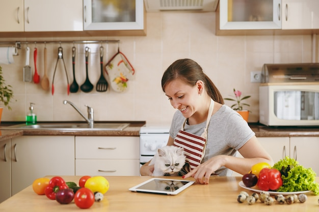 De jonge mooie vrouw met witte perzische kat in de keuken met tablet op tafel. groentesalade. dieet concept. gezonde levensstijl. thuis koken. eten koken.