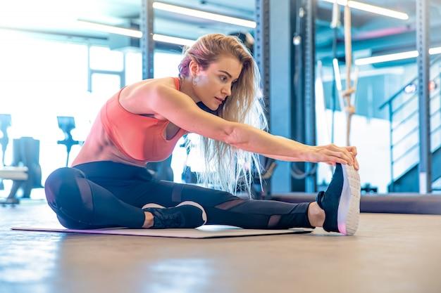 De jonge mooie vrouw rekt zich in de gymnastiek vóór oefening uit
