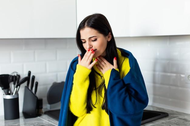 De jonge mooie vrouw voelt zich ziek ziek status in de keuken