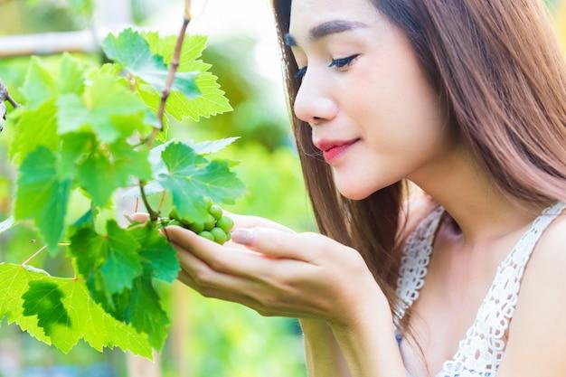 De jonge mooie vrouw waardeert de druivenboom gelukkig