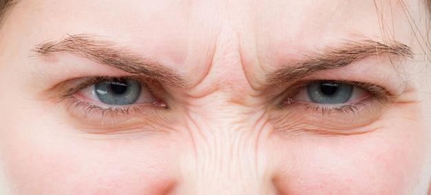 De jonge mooie vrouwen blauwe ogen sluiten omhoog. boze uitdrukking